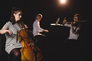 Three female students playing double bass, violin and piano
