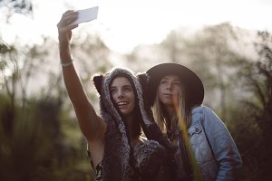 Female friends talking selfie on mobile phone