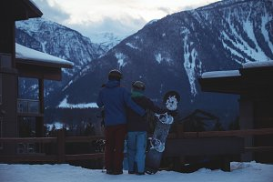 Couple with snowboard standing on snow covered field