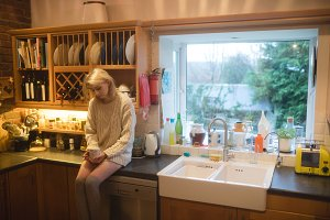 Woman having coffee in kitchen