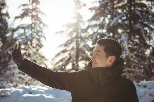 Smiling man taking selfie on mobile phone