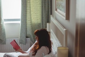 Pregnant woman reading book on bed