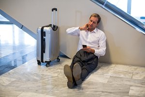 Businessman sitting on floor and using mobile phone in waiting area
