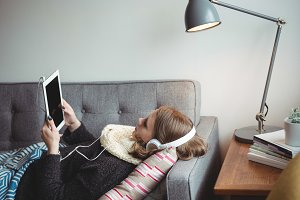 Woman lying on sofa listening to music on digital tablet