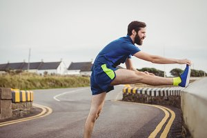 Athlete stretching his leg on the road