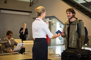 Man interacting with female staff with luggage kept on conveyor belt