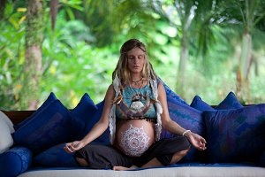 Caucasian pregnant woman with dreadlocks in boho style. White mehendi on big belly. Expectation of baby in new age lifestyle.