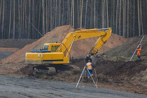 Reconstruction of the road in countryside - yellow excavator at work
