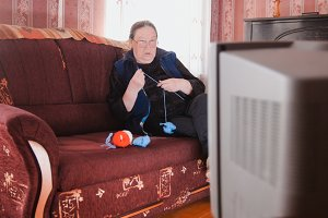 Old lady pensioner at home in glasses knitting in front of the TV