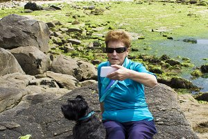 Senior woman doing a selfie with cellphone  with dog