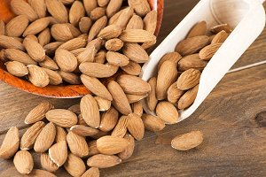 Close-up of almonds inside a bowl and wooden bowl. Horizontal shoot.