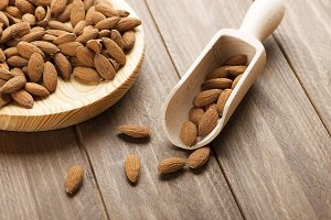Almonds and bowl on wooden plate. Food.