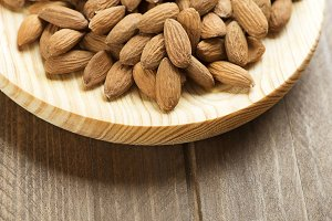 Close-up of almonds on wooden plate. Copy space.