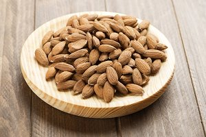 Almonds on wooden plate. Food.
