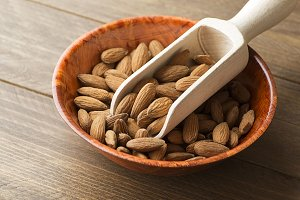 Almonds inside a bowl and wooden bowl. Horizontal shoot.