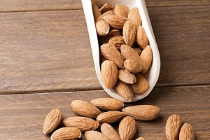 Almonds and wooden bowl. Vertical shoot.