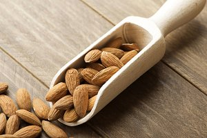 Close-up of almonds and wooden bowl. Horizontal shoot.