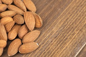 Almonds on wooden table. Copy space.