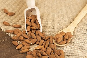 Almonds and wooden containers on canvas. Food.