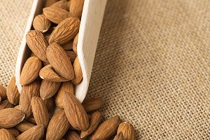 Close-up of almonds and wooden bowl on canvas. Horizontal shoot.
