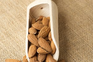 Almonds and wooden bowl on canvas. Vertical shoot.