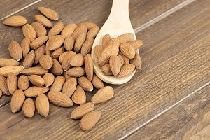 Almonds on wooden spoon. Food.