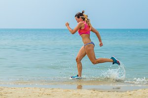 beautiful athletic girl running on the beach, healthy lifestyle