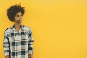 Pensive black girl near yellow wall