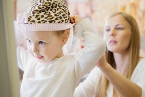 Mom helps her daughter wear a hat