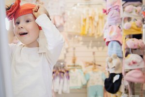 The girl tries on orange beret in front of the mirror
