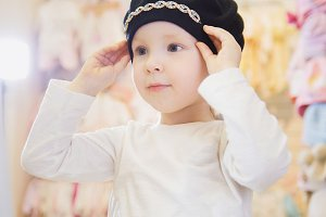 Lovely girl tries on a black beret