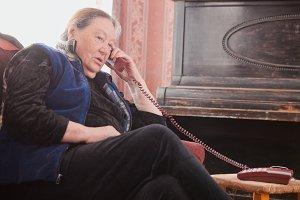 Elderly woman talking on the house phone
