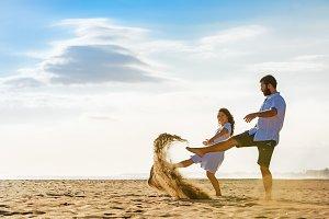 Happy couple walks on sea beach