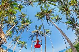 Girl flying high on rope swing
