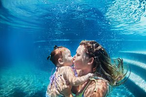 Mother with child swim underwater