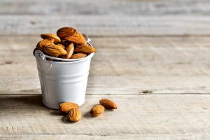 Almonds on wooden background in a bucket . healthy, tasty