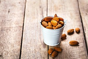 Roasted grains of peanuts in a wooden bucket isolated