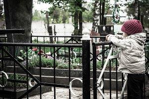 girl near grave in the cemetery