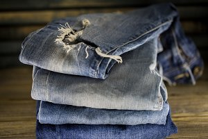 different jeans folded on a wooden background