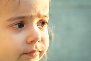 tears the emotions a little girl, on the grey grass