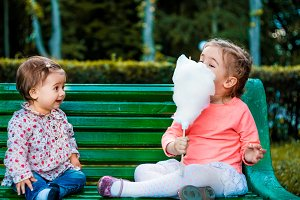 little girl with cotton candy while sitting