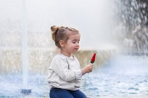 the emotions of a little girl with candy on stick near the fountain