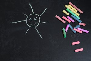 colored chalks, black blackboard with drawings of the sun