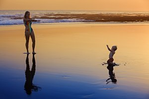 Mother with son on sunset sea beach