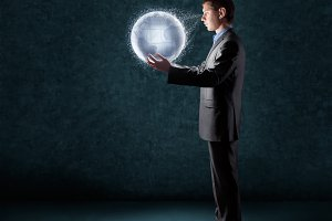 businessman holding glowing planet