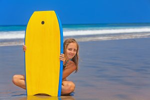Girl with bodyboard on the beach