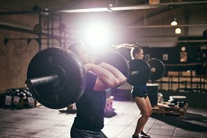 Sportive people lifting heavy barbells in gym