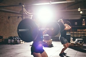 Man and woman lifting barbell in gym