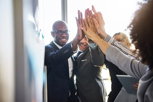Group of business people high five looking positive