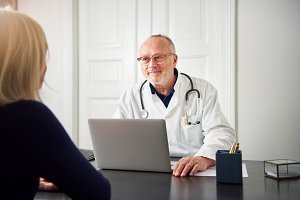 Therapist listening to patient at laptop in hospital